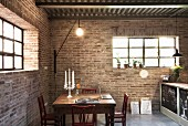 Candlesticks and laptop in illuminated dining area with brick walls in converted stable