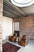 Two vintage leather armchairs on concrete floor against brick wall