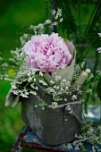 Tin can filled with peonies and flowering chervil on garden chair