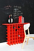 Red wine rack against below recipe written on chalkboard wall
