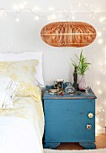 Old, blue, shabby-chic bedside cabinet against board wall