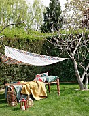 Comfortable lounger under striped awning in garden