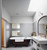Free-standing bathtub against half-height wooden cladding in bathroom