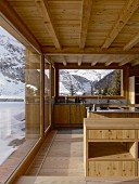 Kitchen in modern wooden house with view of wintry landscape