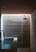 Concrete béton-brut walls and bathtub in bathroom