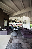 Persian rug in shades of grey and purple sofa set in open-plan interior with white-painted wooden ceiling