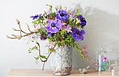 Spring bouquet of blue anemones and magnolia branches