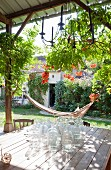 Wooden table and hammock on roofed terrace