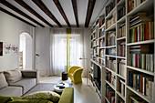 Wohnzimmer mit großer Bücherwand und Balkendecke