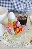 Tulpenblüten in Glasschälchen auf Ostertisch