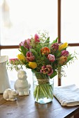 Üppiger Tulpenstrauss mit zarten Mimosen in Glasvase, daneben Porzellanhasen