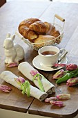 Rolled linen napkins tied with tulips petals and green lace ribbons on aster breakfast table