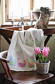 Hand-made table runner with pattern of hens on tray table and potted hyacinths on chair