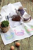 Hand-made table runner with pattern of hens, potted plant, cake and coffee set