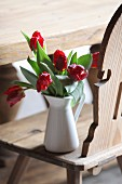 Red tulips in white jug