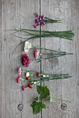 Pinks, grasses, carnations, spray carnations and raspberry leaves on wooden surface