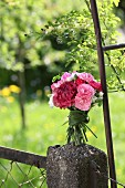 Bouquet of carnations tied with grasses on stone pillar