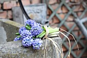 Bouquet of hyacinths tied with raffia on edge of stone fountain