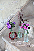Asters and autumn grasses in small glass bottles and circlet of rose hips decorating stair tread