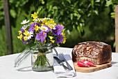 Blumensträußchen im Einmachglas auf dem Tisch mit Brot
