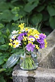 Cottage garden flowers and ears of cereal in preserving jar