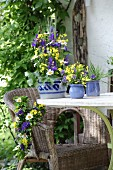 Arrangement of purple and yellow flowers on garden table and wicker armchair