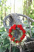 Wreath of red zinnias and switchgrass hung from weathered wicker armchair