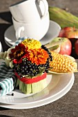 Arrangement of zinnias and dogwood berries wrapped in maize leaves