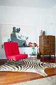 Red designer easy chair on zebra-skin rug