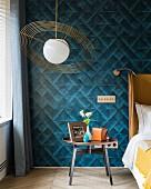 Schlafzimmer mit Retro Pendelleuchte und petrolfarbener Textiltapete mit geometrischem Muster