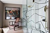 Bad Ensuite mit Marmorwänden und Glasabtrennung neben gerahmtem Bild und Armlehnstuhl