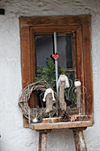 Hand-crafted driftwood angels on wooden stool in front of window