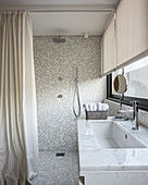 Marble sink in front of walk-in shower area with mosaic tiles