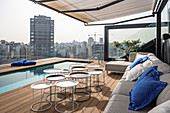 Long narrow swimming pool and sofa combination on roof terrace with view of city