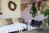 Mediterrane Loggia mit Sofa, Esstisch und lilafarbener Wand