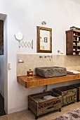 Stone sink and old wooden crates used for storage in bathroom