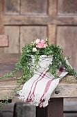 Blumengesteck mit Rosenblüten und Efeuranken auf rustikalem Holztisch