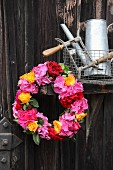 Wreath of hydrangeas and roses in shades of red and orange hung on old wooden door