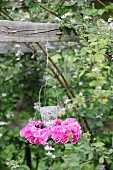 Candle lantern in wreath of pink hydrangeas hung from wooden beam