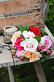 Bouquet of roses in various colours on weathered wooden table