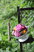 Hydrangeas and roses in vintage-style colander hung from fence