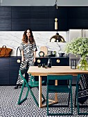 Eat-in kitchen with black and white patterned floor tiles and black kitchen cupboard, young woman in the background