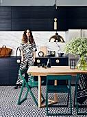 Wohnküche mit schwarz-weiss gemusterten Bodenfliesen und schwarzem Küchenschrank, junge Frau im Hintergrund