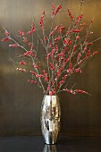 Branches of red berries in gold vase