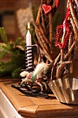 Christmas arrangement of rustic twig wreath, candle, rocking horse ornament and old bundt cake tin