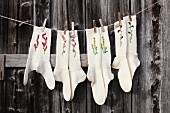 Hand-knitted woollen socks embroidered with flowers hung from washing line
