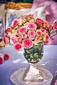 Elegant vase of roses on garden table