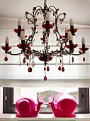 Zwei pinkfarbene Schnecken aus Kunststoff auf Fenstersims unter romantischem Kronleuchter