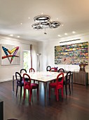 Velvet chairs around table in front of sideboard and modern artwork