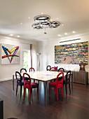 Samtstühle am Tisch vor Sideboard und buntem, modernem Bild